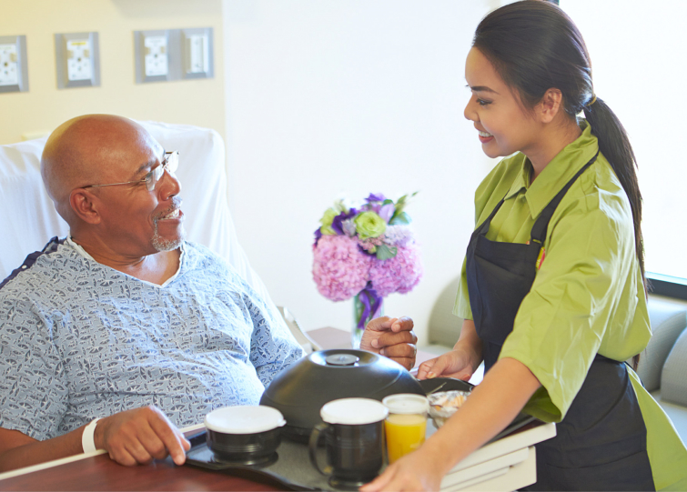caregiver delivering a meal to an elderly man