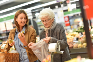 woman assisting senior woman doing a grocery shopping